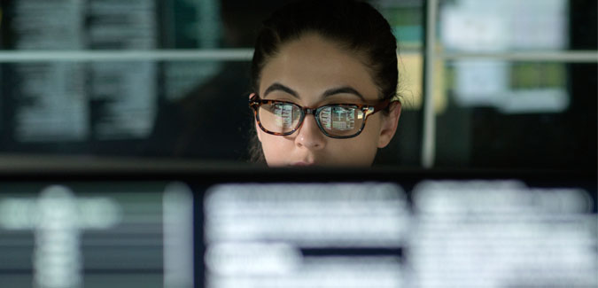 A young woman works on a computer.
