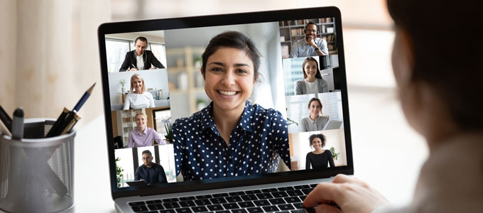 A woman attends a virtual meeting on her laptop.